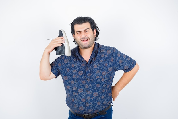 Middle aged man holding shoe over shoulder in shirt and looking serious , front view.