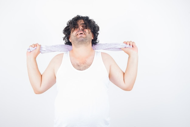 Uomo di mezza età che tiene un asciugamano sul collo in canottiera, asciugamano e sembra felice, vista frontale.