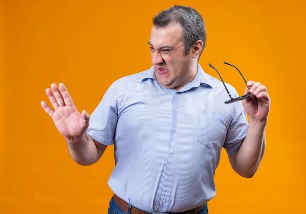 Мужчина средних лет в синей полосатой рубашке, выражающий иронию и ненависть, демонстрирует недовольство, держа солнцезащитные очки на оранжевом фоне