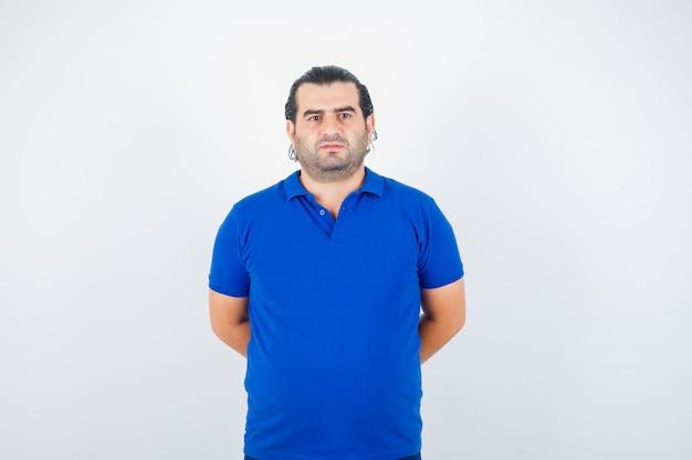 後ろで手を握り、自信を持って、正面図を見て青いtシャツの中年男性。