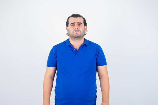 カメラを見て、物欲しそうな正面図を見て青いtシャツの中年男性。