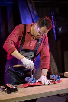 自宅のワークショップで赤いプラスチックの子供スケートボードを修正するジャンプスーツの中年男
