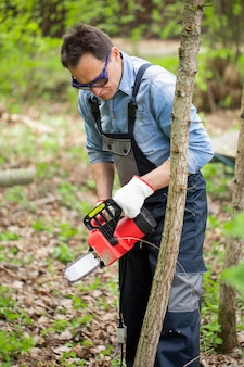 Мужчина средних лет в комбинезоне пил по дереву с цепной пилой на фоне вырубки опавших листьев