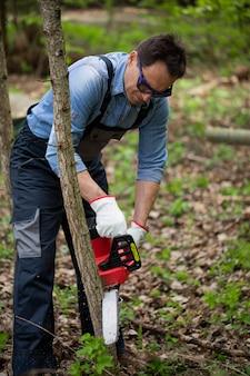 Мужчина средних лет в комбинезоне пил по дереву с цепной пилой на фоне опавших листьев