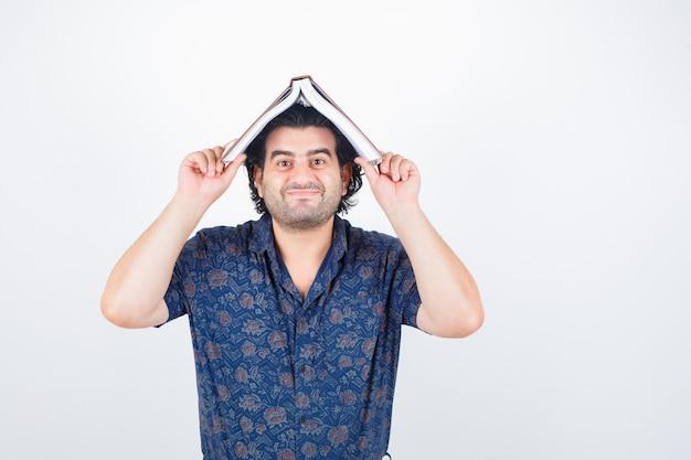 家の屋根として頭に本を持って、面白い、正面図を見てシャツを着た中年の男性。