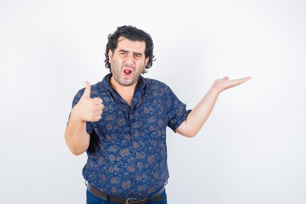 親指を立てて喜んで見ながら何かを持っているシャツを着た中年男性、正面図。