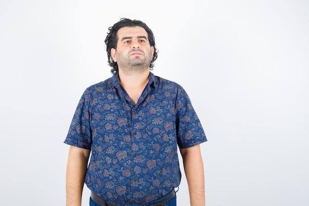立って自信を持って見ながら目をそらしているシャツを着た中年男性、正面図。