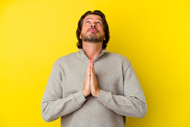 Middle aged man isolated on yellow wall holding hands in pray near mouth, feels confident