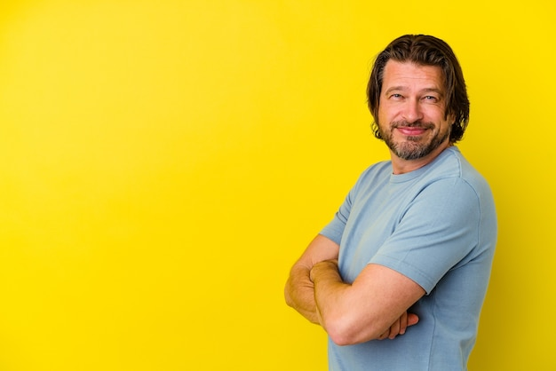 Middle aged man isolated on yellow wall smiling confident with crossed arms