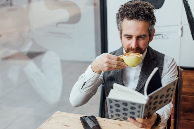 Middle aged man jewish nationality spends afternoon or morning in trendy or hipster coffee shop