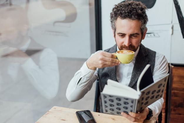Мужчина средних лет еврейской национальности проводит день или утро в модной или хипстерской кофейне.