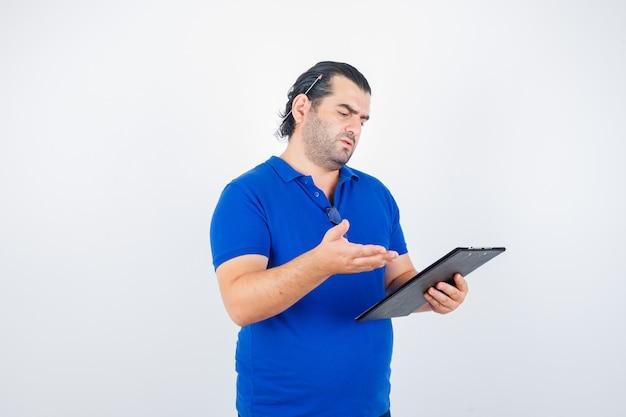 中年男性がクリップボードを保持しながら、ポロtシャツで疑わしい方法で手のひらを広げ、物思いにふける、正面図。