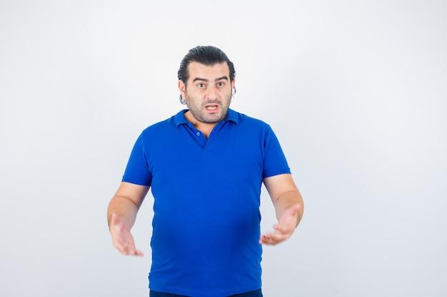 파란색 티셔츠에 적극적인 방식으로 손을 유지하고 의아해 보이는 중간 세 남자. 전면보기.