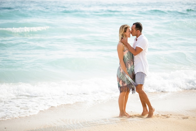 Middle-aged man kissing wife on sunny beach