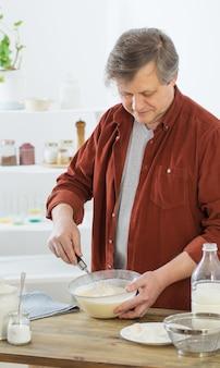 Мужчина средних лет замешивает тесто для блинов на белой кухне