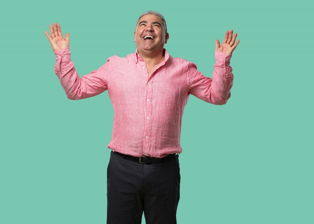 Middle aged man laughing and having fun, being relaxed and cheerful, feels confident and successful