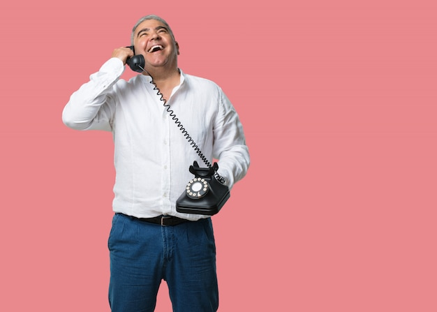 Middle aged man laughing out loud, having fun with the conversation, calling a friend or a client