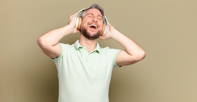 Middle aged man listening music with his headphones