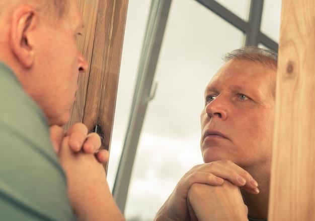 鏡の反射を真剣に見つめ、年齢や人生を考えている中年男性。