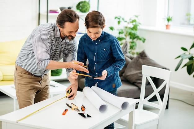 息子の隣に立って、目の前のテーブルに絵を描いている間、タブレットの画面を見ている中年の男性