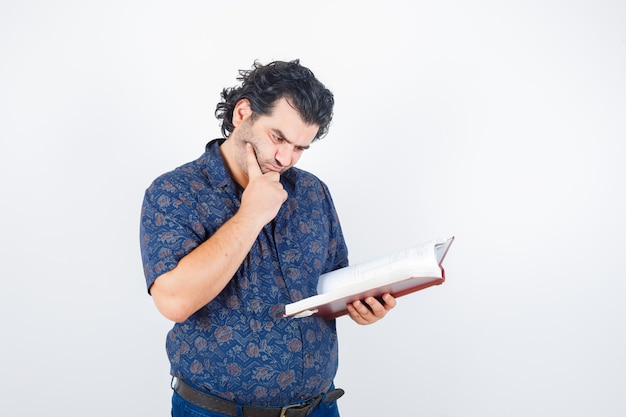 Middle aged man looking at book in shirt and looking pensive. front view.