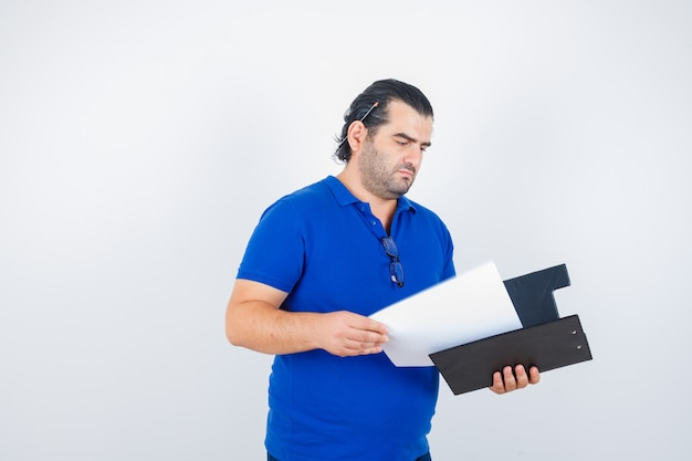 Middle aged man looking over documents in clipboard in polo t-shirt and looking focused , front view.