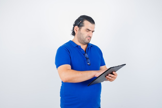 Middle aged man looking over documents in clipboard in polo t-shirt and looking focused. front view.