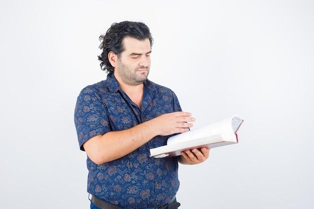 シャツを着た本をのぞき、集中して見ている中年男性、正面図。