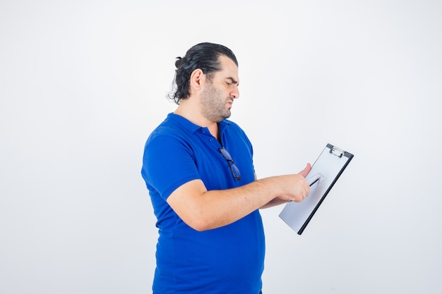 Middle aged man looking through clipboard while holding pencil in polo t-shirt and looking thoughtful , front view.