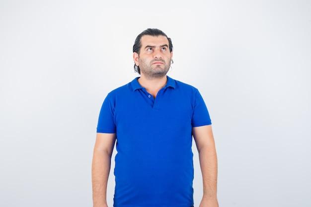 파란색 티셔츠를 찾고 사려 깊은 찾고 중간 세 남자. 전면보기.