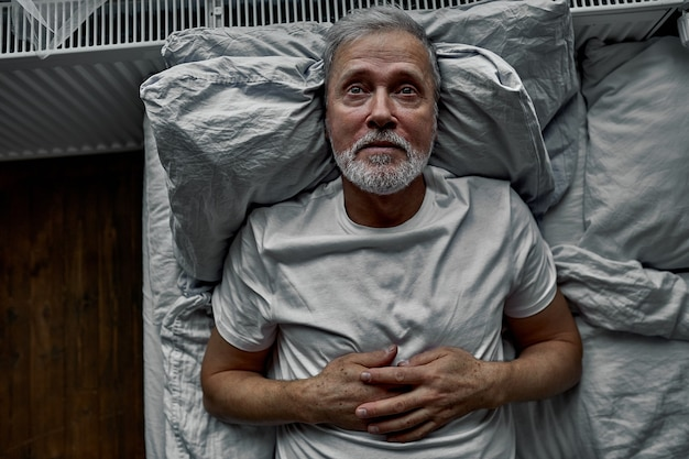 枕の上でベッドに横になって、不眠症の睡眠障害を持っている中年の男性。家で独り