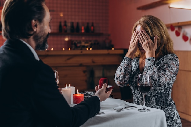 A middle aged man makes a marriage proposal to a woman at dinner