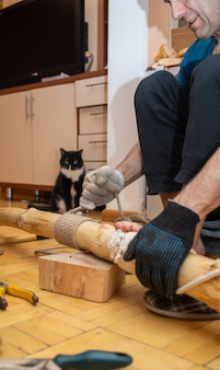 Middle-aged man making climbing tree for cat while sitting on floor at home. he winding sezal rope around cleared tree trunk. cat is watching process. homemade cat tree for lovely pet. vertical photo.