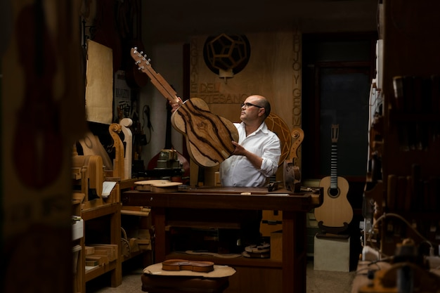 Middle aged man making instruments in his workshop alone