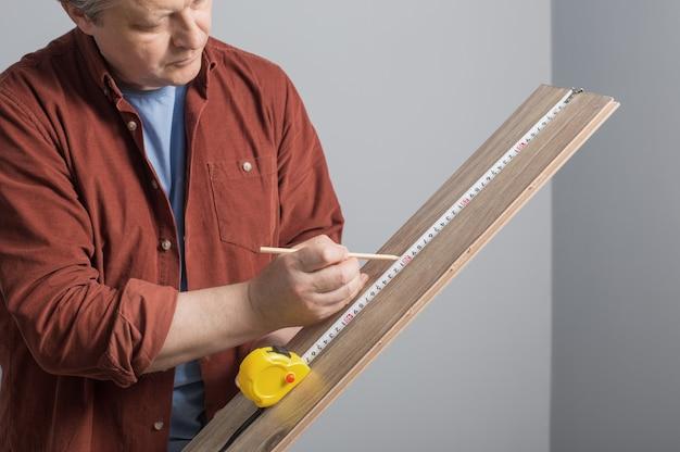 건설 테이프로 라미네이트 보드를 측정하는 중간 세 남자