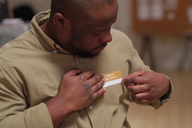 胸に自分の名前のバッジを置き、心理的なセッションの準備をしながらそれを見ているアフリカ民族の中年男性