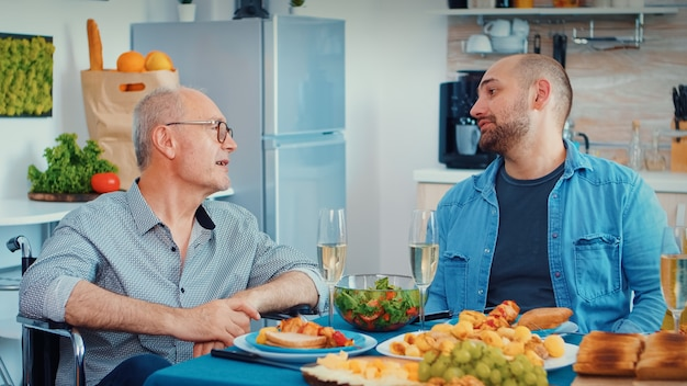 Middle aged man and older senior in wheelchair having fun during family dinner. happy men smiling, drinking and eating during a gourmet meal, enjoying time sitting around the table in the kitchen