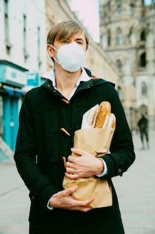 Мужчина средних лет на улице с хлебом, багетом, покупкой буханки во время глобальной пандемии, в маске, достает хлеб из пекарни. еда с собой, покупка булочных во время covid 19.