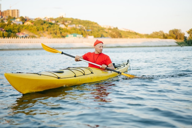 Middle aged man in orange watch cap riding on yellow kayak on a big wide river. reinforsed shoreline, trees and some houses in a distance.
