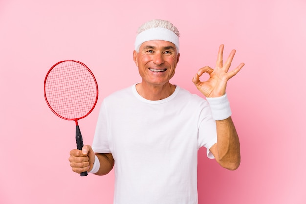 Middle aged man playing badminton isolated cheerful and confident showing ok gesture.