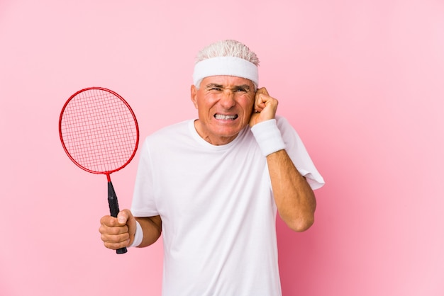 Middle aged man playing badminton isolated covering ears with hands.