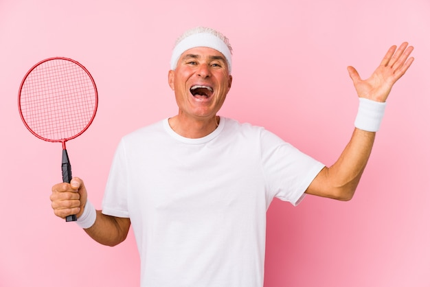 Middle aged man playing badminton isolated receiving a pleasant surprise, excited and raising hands.