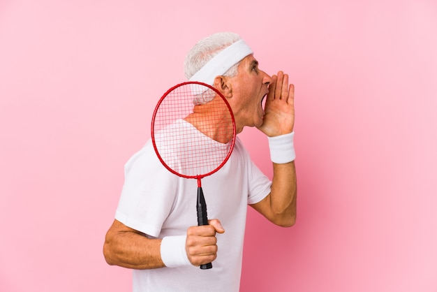 Middle aged man playing badminton isolated shouting and holding palm near opened mouth.