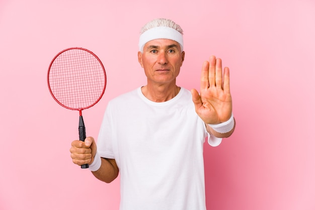 Middle aged man playing badminton isolated standing with outstretched hand showing stop sign, preventing you.