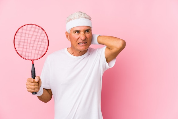 Middle aged man playing badminton isolated touching back of head, thinking and making a choice.