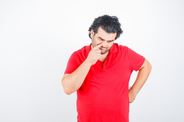Middle aged man poking his nose in red t-shirt and looking thoughtful , front view.
