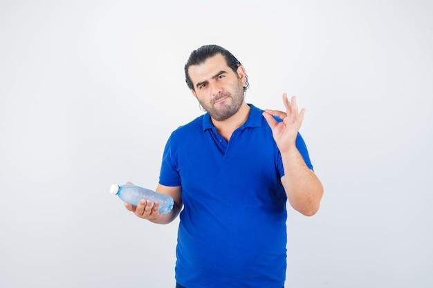 Uomo di mezza età in t-shirt polo che tiene una bottiglia d'acqua mentre mostra il gesto giusto e sembra esitante, vista frontale.