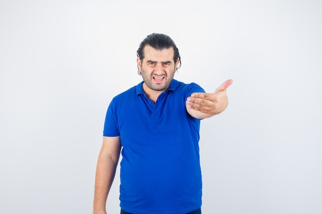 Middle aged man in polo t-shirt inviting to come and looking angry , front view.