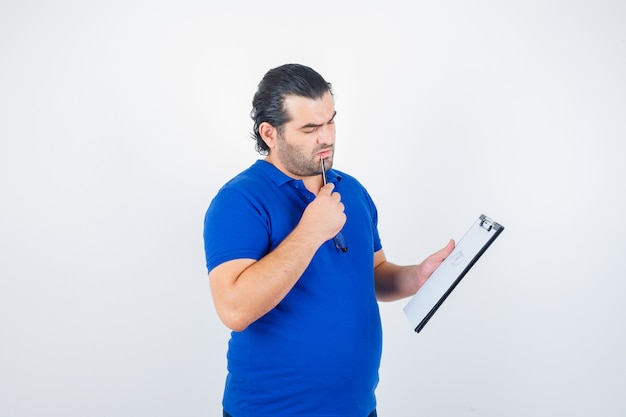 Middle aged man in polo t-shirt looking through clipboard while holding pencil on mouth and looking pensive , front view.