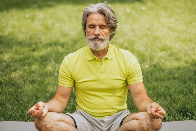 Middle aged man practicing yoga on mat in park